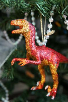 Glitter dinosaur toys as ornaments ~ I have some old dinosaurs around that might just like a coat of glitter!