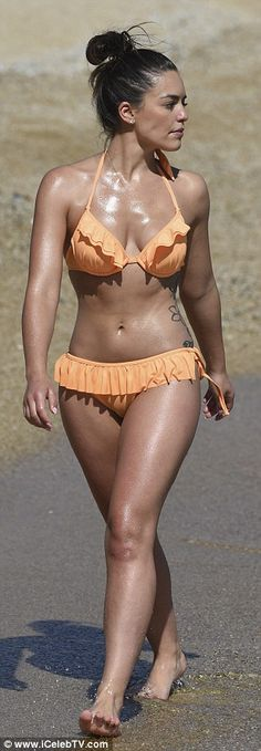 The 23-year-old Australian beauty, the half-sister of singer and actress Holly Candy, looked absolutely phenomenal in a frilled orange bikini which made the most of her ample bosom and incredible abs
