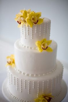 all white cake with yellow orchid and piped detail. Would love it with daffodils