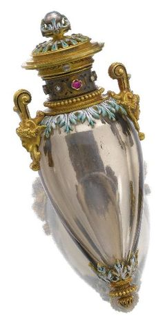 Gem set and enamel perfume flask, circa 1900. Designed as an amphora, the body composed of carved smoky quartz, the neck and lid set with a seed pearl, oval rubies and rose diamonds, with enamel, fitted case.