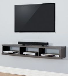 Tv on the wall with remote and PlayStation on a cabinet