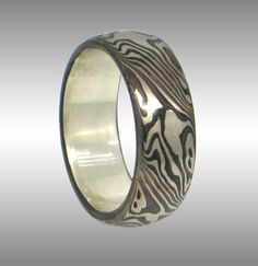 Elegant Mokume Gane Ring with Contrasting Pattern. 14k palladium white gold and Sterling silver Mokume with a Sterling Silver lining. Shown in a size 7, with a 7mm width.