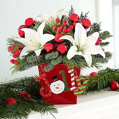 Deluxe Holly Jolly Centerpiece - Add instant holiday pop to the room with our Holly Jolly Centerpiece. Fragrant and fun, this centerpiece features white Asiatic lilies, cedar, Douglas fir, pine, noble fir and is topped with red mini Christmas ball picks.