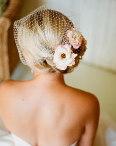 A birdcage veil, accented with fresh blooms