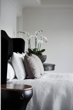 Master bedroom, black velvet headboard which wraps onto the cupboards like a winged style, the drum black body, white orchid , white quilt , simple,  with mix of texture