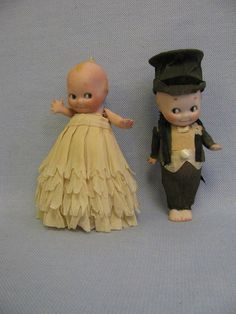 "1920's 4 1/2 "" all-bisque pair of wedding cake toppers in their original crepe paper wedding clothes"