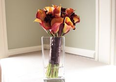 This hand tied fall bridal bouquet features 25 mango mini callas, 20 chocolate cosmos, and a chocolate satin stem wrap. The chocolate color added by the cosmos transforms this typical fall color scheme into a rich and romantic color palette. Surprisingly, the delicate chocolate cosmos are prized more for their chocolate scent than their color.