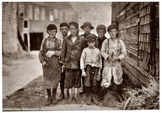 August 1911, Eastport, Maine. All these boys are cutters in the Seacoast Canning Co., Factory #7. Ages range from 7 to 12. Seven year old boy in front, Byron Hamilton, has a badly cut finger, but helps his brother regularly. Behind him is his brother George, 11 years. He cut his finger half off while working. They and many other youngsters said they were always cutting their fingers. George earns $1 some days, 75 cents usually. Some of the others said they earn $1 when they work all day. At…