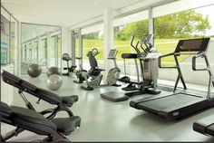 Coworth Park's gym has plenty of natural light and tree top views. The Technogym cardiovascular equipment has integrated televisions and includes three treadmills in this wellness area. #wellnessinhotels #technogym