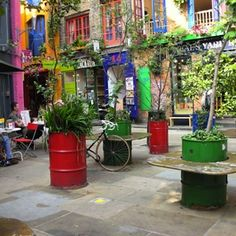 Astounding Covent Garden Design Including Colorful Oil Drums As Planters For Flower And Trees Completed With Built In Wooden Bar For Lounge Space Recycled Planters, Recycled Garden, Diy Planters, Garden Planters, Urban Planters, Tree Planters, Garden Table, Covent Garden, Oil Barrel