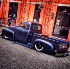 blacked out 1952 1953 Chev Chevy Chevrolet Advance Design pickup in a satin black flat black paint job with touches of pinstripping and vintage truck in the bed. The whole package is laid out slammed dropped over a set of wide white wall tires and black steel wheels with spider caps.