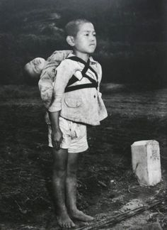 """Japanese orphan, standing at attention having brought his dead younger brother to a cremation pyre, Nagasaki, 1945. Photo by Joe O'Donnell. This is O'Donnell's description of the older boy after the dead brother was placed on the pyre: """"The boy stood there straight without moving, watching the flames. He was biting his lower lip so hard that it shone with blood. The flame burned low like the sun going down. The boy turned around and walked silently away."""""""