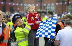 This young man just needed a little help to make sure he saw his heroes during Wigan Athletic Football Clubs FA Cup winners parade. Luckily one of Greater Manchester Polices Police Community Support Officers was able to assist. The moment was captured on camera by Alex Flahive of Greater Manchester Fire and Rescue Service. Big crowds turned out to greet the team in the aftermath of their Wembley win over Manchester City.