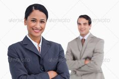 Smiling saleswoman with arms folded and colleague behind her ...  20s, Two People, background, business, businessman, businesspeople, businessteam, businesswoman, career, caucasian, colleagues, cooperation, corporate, elegant, employee, executive, inside, isolated, man, manager, mixed-race, partners, partnership, professional, sales, salesman, saleswoman, staff, standing, suit, team, teamwork, together, trade, tradesman, tradeswoman, white, young