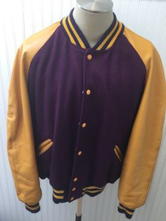 ~~~Up for Grabs~~~Purple wool and gold leather sleeves and matching leather trim at slit front side pockets Vintage Sports Jacket. It features 100% black polyester lining with no stains, striped two toned sock bottom, collar, at end of arm sleeves and 7 gold snaps down front for closure. The colors are a deep purple and a gold mustard yellow. I think these are close to Viking colors.  ~~~This Letterman jacket is blank and ready for your personal and unique customization of your favorite…