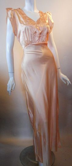 Dreamy sweet peach satin acetate late 1930s bias cut nightgown with trapunto stitching. Mother of pearl buttons at center of sweetheart neckline, shirred at shoulders, ruffle sleeves. Sashes at side seams tie in back.
