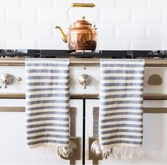 French kitchen features a white French stove draped with white and gray striped Turkish towels under a subway tiled backsplash.