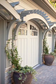 Gorgeous garage door treatment with arched arbors supported by decorative brackets...