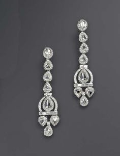 A PAIR OF DIAMOND EAR PENDANTS   Each designed as an articulated line of vari-shaped rose-cut diamonds, within circular-cut diamond surrounds, suspending a similarly-set pendant, enhanced by baguette-cut diamond trim, mounted in white gold