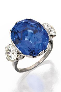 An Early 20th Century Platinum, Sapphire and Diamond Ring. Centred by an oval-shaped sapphire weighing 24.40 carats, flanked by two old European-cut diamonds weighing approximately 3.00 carats. #BelleEpoque #ArtDeco