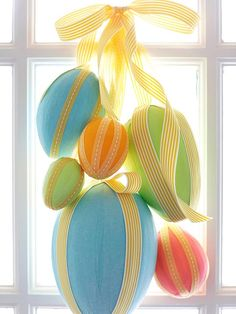 Wrap plastic foam egg shapes (available at crafts supply stores) with strips of crepe paper, attaching ends with glue or a small straight pin. Embellish with ribbon secured using small straight pins, leaving a long end for tying. Gather eggs at varying heights and tie ribbons together. Hang from a removable adhesive hook or wreath hanger, and add a ribbon bow to complete the Easter decoration.