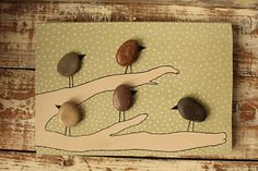 Let these birds be your daily company, hang this pebble art on the wall and you will never feel alone again.  These paintings are unique pieces, the shape of each pebble creates an original and unrepeatable world that you only can live.  Collage of pebbles on wood - hand painted.  Dimensions: 35 cm x 20 cm (LxA)  Complete with wall hanger.