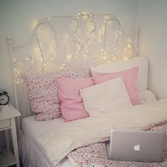 simple pastel pink and white bed with lights
