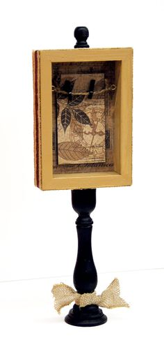 Pedestal Shadow Box - Glue a small frame to a wooden candle stick, paint and wrap with ribbon. #craft #idea #burlap