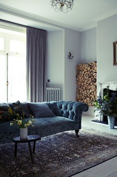 indigo blue sofa, gray walls, vintage rug, wood stacks