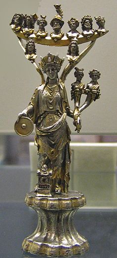 Gallo-Roman Tutela, silver statuette Draped Goddess of the City (see mural crown) holding a twinned cornucopia and a patera; the Dioscouri are on her wings, at the tips of which is an arc holding busts of the gods recognizable by their attributes. A tiny garlanded altar is at her feet. From the Macon hoard. Roman 150-220 CE. London: British Museum.