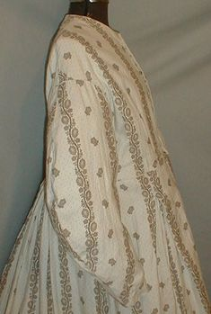1860s cotton print maternity dress.  Fabric has a brown printed pattern on white background that has tiny brown dots.  Neck, armscyes and waist are piped.  Bodice lined with cotton and has front button closure.  Skirt unlined.