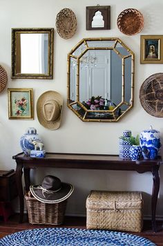 gallery wall of collected baskets, hats, mirrors, paintings, and objets above a console, blue and white pottery, woven baskets under the console