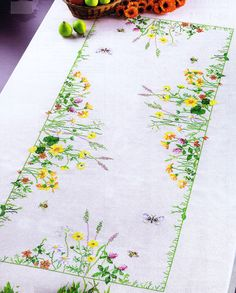A stunning colourful table cover decorated with flowers, butterflies and bees in a central rectangle.