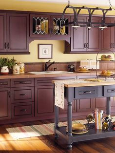 Dark with Detail Add warmth to dark wood cabinets by using warm wall colors and details. Pale golden walls and oak flooring add that warmth while a touch of black (on the island) is a nice balance to the wood.