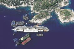 An aerial photo taken in August shows the Costa Concordia as it lies on its side next to Giglio Island. The liner capsized off the Italian coast in January 2012, killing at least 30 people. Workers raised the ship in September in the largest and most expensive maritime salvage operation in history.