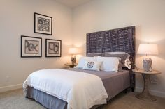 In a more compact guest room, we chose to highlight the height of the room with a stylish and bold headboard and wall art, keeping the bedding more muted with the exception of the decorative pillow.
