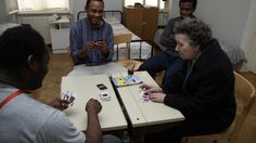 Frau Bock plays cards with refugees in Ute Bock House.