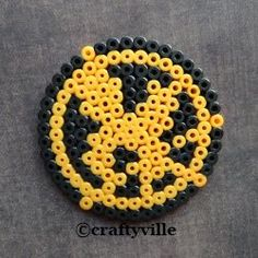 Make your own Mockingjay token with the plastic beads that melt using an iron.