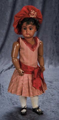 Fine German Brown-Complexioned Bisque Child. by Kestner with Original Costume ~~~Marks: E made in Germany 9. Comments: Kestner, circa 1900. Value Points: flawless complexion on the beautiful face, perfect original body, wig, and pate, nice antique red and white costume is likely original.