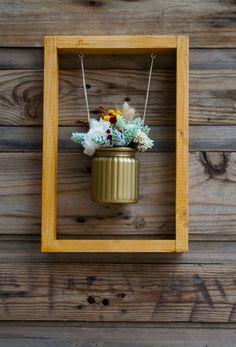 Flores preservadas y secas en un bote de cristal pintado de dorado
