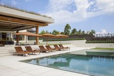 Steps from the living pavilion lead to a stone deck and sunbrella-shaded loungers.