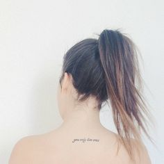 """Upper back tattoo saying """"You only live once"""" on Úrsula Campos."""