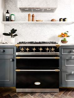 Marble back-splash, black oven with gold hardware #kitchen