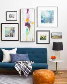 Black framed gallery wall with vibrant art in living room with navy sofa, leather poof, gray rug, and small white side table