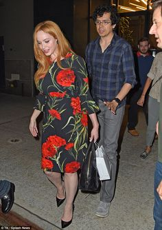 Flower power: The stunning redhead wore a red carnation-themed frock and black pumps for h...