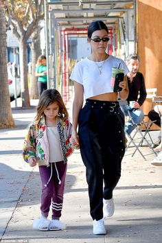 Super cute!Kourtney's daughter Penelope looked adorable in a bright floral bomber jacket teamed with trackies while she toted her vanilla ice cream