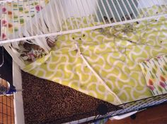 Piece of fleece over the wood pellets. The fleece muffle the noise and create a softer surface, while wicking urine through the very absorbent pellets. Twice a day, I simply roll up the fleece, take it outside, shake off the poops and hay, and lay it back down all nice and clean.  The cage is completely odor-free, even though I haven't changed the wood pellets for a full 3 weeks.
