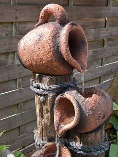 """Another interesting water fountain design which is basically made out of old wood logs with straw ropes, and 3 pieces of miniature terracotta water jugs. These water jugs are placed on top of multi-leveled logs, and the water flows from one jug to another through a """"cracked"""" opening on top of the lower jars. This is ideal for those who doesn't want to maintain a large water feature in their garden, but wants to have a flowing water element."""