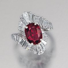RUBY AND DIAMOND RING.  Centring on a cushion-shaped ruby within a stylised ballerina surround set with tapered baguette diamonds, mounted in platinum