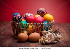Traditional Romanian Easter Colored Eggs - Basket with colorful Easter eggs on red background. by eZeePics Studio, via Shutterstock